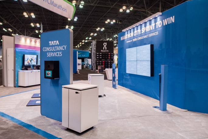 blue expo booth with a screen and a table