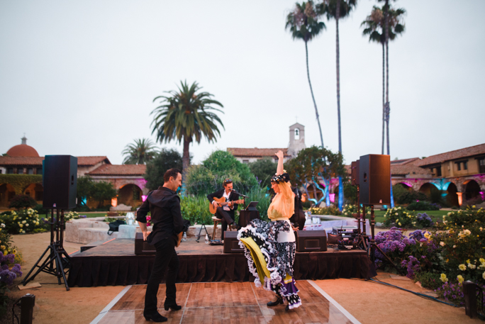 A couple dancing next to palm trees and a band playing