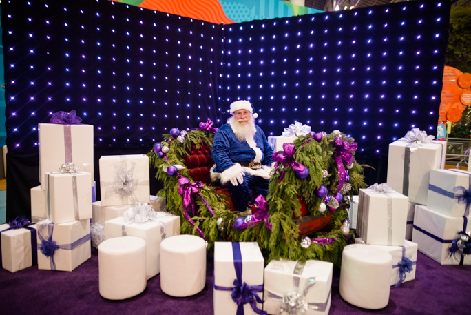 Santa surrounded by white gift boxes