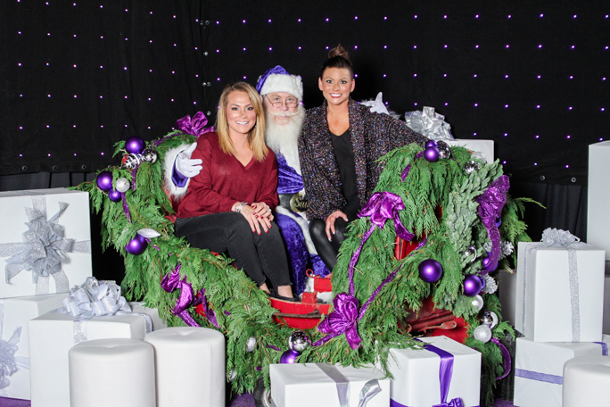 Santa with two women surrounded by gift boxes