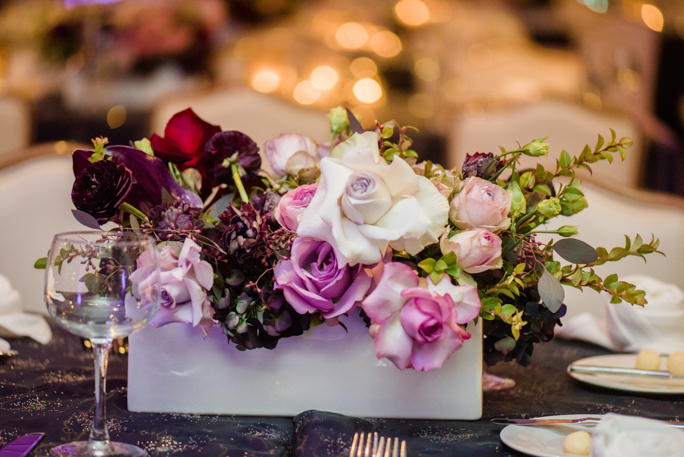 A centerpiece with roses on a table