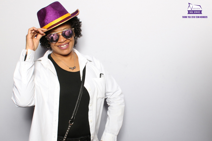 a photo of a woman wearing sunglasses and a purple hat