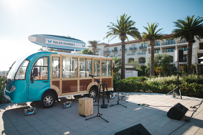 A bus next to microphone and palm trees