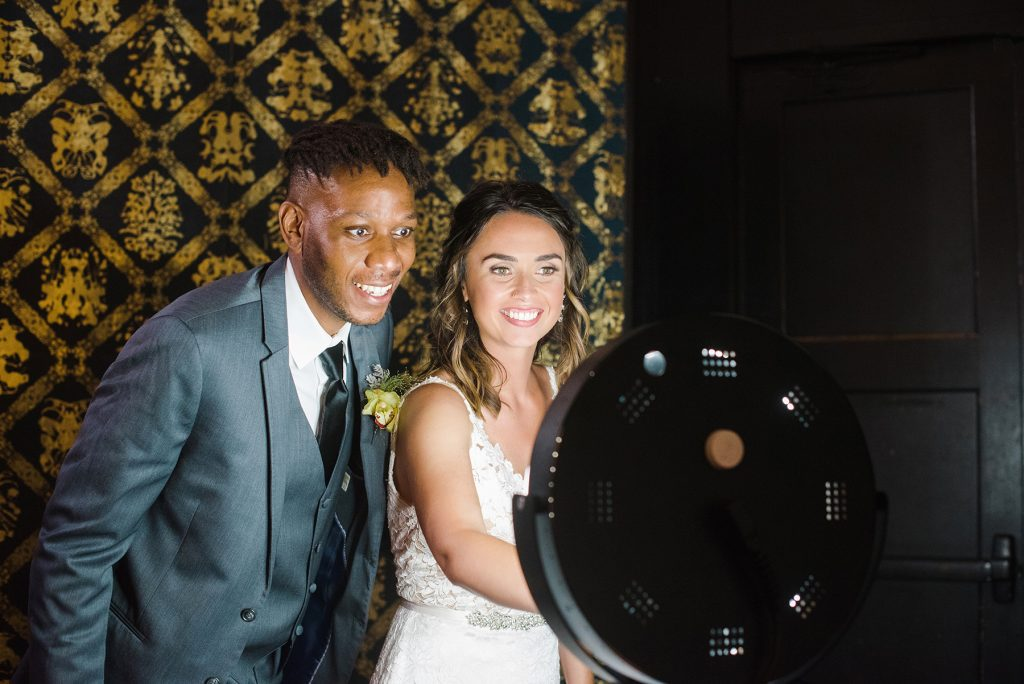 A bride and groom using a drop-off photo booth