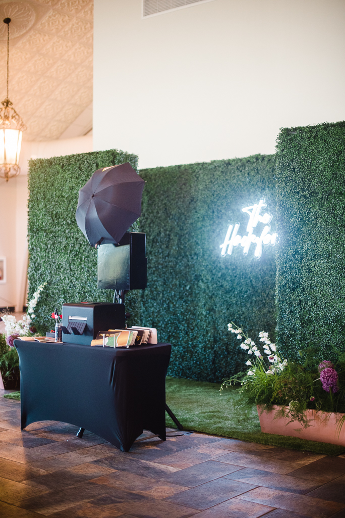 An open style booth by a hedge backdrop
